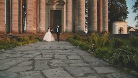 Desfiladero de los pares preciosos de la boda en pista en el castillo hermoso antiguo almacen de metraje de vídeo