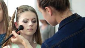 Desfile de moda de bastidores, maquilhador e cabeleireiro fazendo o cabelo, a denominação e a composição de uma menina bonita, pu filme