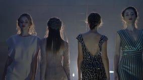 Desfile de moda, mujeres jovenes en ropa elegante y zapatos de tacón alto en escena encendida almacen de metraje de vídeo