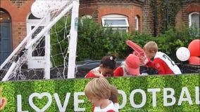 Desfile del flotador del equipo de fútbol de los niños en carnaval de la calle