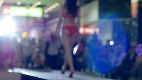 Desfile dos modelos na mostra do roupa de banho no pódio, desfile de moda, apresentação do roupa de banho na passarela da forma, video estoque