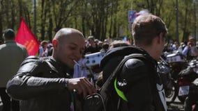 Desfile y demostración de los motoristas en cuadrado Dos individuos fuman almacen de video