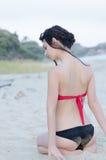 Desgaste bonito delgado joven de la señora rojo y bikini negro que se sienta en las piernas en la arena imagenes de archivo