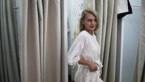Desgaste de mujer el vestido blanco en el guardarropa Muchacha europea de moda que mira en el espejo en sitio apropiado Jóvenes y almacen de video