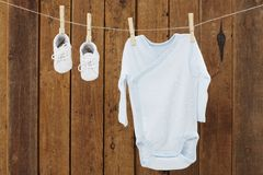 Desgaste do bebê que pendura nos pregadores de roupa na linha de lavagem Foto de Stock Royalty Free