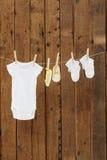 Desgaste do bebê que pendura nos pregadores de roupa na linha de lavagem Imagens de Stock Royalty Free