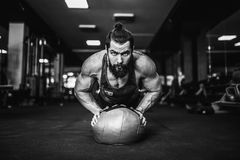 Desgaste Muscled do esporte vestir de homem novo e fazendo a posição da prancha ao exercitar sobre o assoalho no interior do sótã imagens de stock royalty free