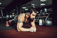 Desgaste Muscled do esporte vestir de homem novo e fazendo a posição da prancha ao exercitar sobre o assoalho no interior do sótã imagens de stock