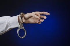 Deshonesto y un tema del doctor de la prisión: la mano del hombre en una camisa blanca con las esposas en un fondo azul marino en Foto de archivo