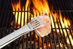 Deshuese el filete, las pinzas y la rejilla caliente del Bbq con las llamas Fotos de archivo