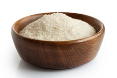 Desiccated coconut in dark wooden bowl. Royalty Free Stock Photography