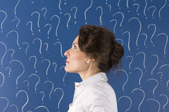 Desicions. Thinking woman in front of question marks Royalty Free Stock Photo