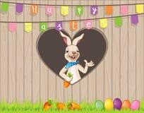 Desiderio del coniglietto di pasqua voi Pasqua felice con le uova e carote dietro il recinto sul foro di forma del focolare - man Immagine Stock
