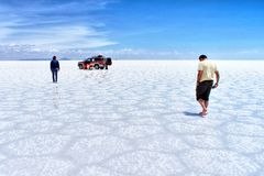 Desierto de la sal de Salar de Uyuni Bolivia - hombres y coche Imágenes de archivo libres de regalías