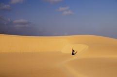 Desierto, dunas, cielo azul, día soleado en la distancia un viajero Foto de archivo