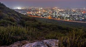 Desierto en la noche con las luces de la ciudad Fotos de archivo libres de regalías