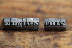 Design this. The word design this in letterpress type on a wooden background stock images