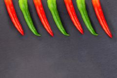 Design base long pods of hot pepper vegetable part bright red green border on black substrate stock images