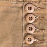 Design botton of brown shirt on fabric textile. Background Royalty Free Stock Images