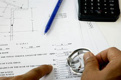 Design Calculation. Engineer check his Design Calculation with calculator and machine parts royalty free stock photo