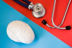 Design concept of diagnosis and detecting diseases of nervous system organ - brain. Stethoscope and model of brain are opposite on. Red and blue background stock photography