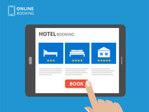 Design concept of hotel booking online. Tablet computer with hand touching a screen. Display with book button and bed. Icons. Mobile application for renting Stock Images