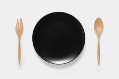 Design concept of mockup black dish, wood spoon and wood fork set. Isolated on white background. Copy space for text and logo. Clipping Path included on white Royalty Free Stock Photo
