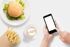 Design concept of mockup using smartphone with burger, french fries and coffee set  on white background. Stock Photo