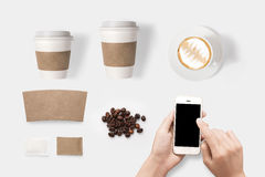Design concept of mockup using smartphone and coffee set isolated on white background. Copy space for text and logo. Royalty Free Stock Photo