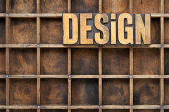 Design concept in wood type. Design word in vintage letterpress wood type against divider pattern of a grunge typesetter case Royalty Free Stock Photos