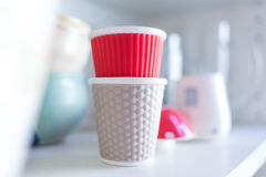 design cups on bright shelf Royalty Free Stock Image