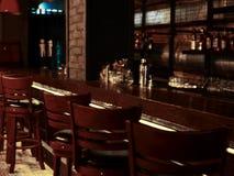 Design de interiores da barra do jazz moderno, fase com piano preto e violoncelo, lâmpadas acima do contador da barra fotografia de stock royalty free