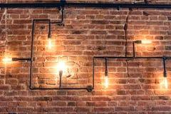 Design der Weinlesewand Rustikales Design, Backsteinmauer mit Glühlampen und Rohre, niedriger beleuchteter Stangeninnenraum Lizenzfreies Stockbild