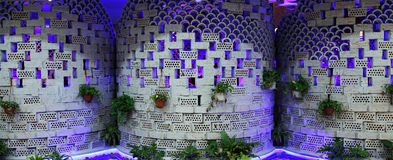 Design the exterior wall of a restaurant. Perforated bricks and arc tiles, like basketball and bottles of wine, the wall of the purple light and vase Stock Image