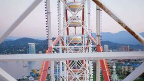 The design of the Ferris wheel with the height of raised booths. The wheel moves and picks up people on it. stock video