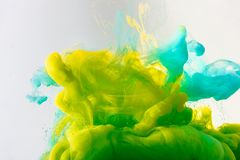 Design with flowing turquoise, yellow and green paint in water, isolated on grey royalty free stock images