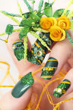 Design green acrylic nails with yellow roses . Royalty Free Stock Photos