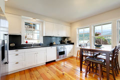 Design of kitchen room interior with white cabinets and black counter tops. Tall wooden dining table with chairs. Northwest, USA Royalty Free Stock Photography