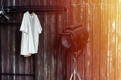 Design of loft Interior of dressing room. Metal wall and cinema lightning and white t-shirt on background. Sunlight Stock Photography