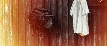 Design of loft Interior of dressing room. Metal wall and cinema lightning and white t-shirt on background. Sunlight Royalty Free Stock Photography