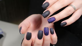Design of manicure matt black and blue nails Stock Photo