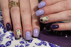 Design of manicure purple with a pattern of flowers. Here is presented one of the best manicure designs this year& x27;s Nail royalty free stock photos