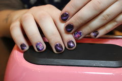 Design of manicure purple with a pattern of flowers. Nails stock photos