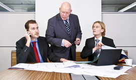 Design meeting. Two junior architects and a senior manager going over the final details of a design in a cubicle Royalty Free Stock Image