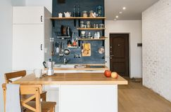 Design of modern home kitchen in the attic and rustic style. Black wall with shelves, trays, jars, mugs. Refrigerator, dining tabl. E, corridor, brick wall, door Royalty Free Stock Images