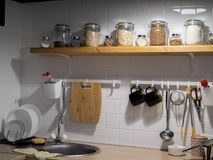 Design of modern home kitchen in the loft and rustic style. Black wall with shelves, trays, jars, mugs, sink. Against a. Wall with photos of a couple and a royalty free stock photos