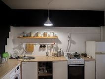 Design of modern home kitchen in the loft and rustic style. Black wall with shelves, trays, jars, mugs, sink. Against a. Wall with photos of a couple and a stock photos