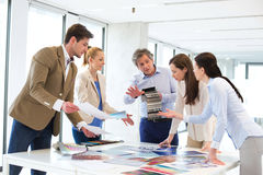 Design professionals with catalogs discussing at table in new office Stock Images
