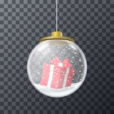 Red present inside of glass bauble. Design of round crystal glass bauble filled with snow and Christmas gift box Stock Photo