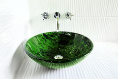Design sink with running water. Great bathroom design with faux marble glass vessel sink on corrugated white ceramic tile with water running of modern wall Royalty Free Stock Images